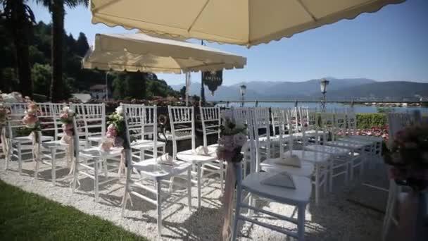 Bílé svatební židle v otevřené obřadu s květy a ornamenty v Itálii