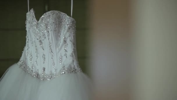 White wedding dress with rhinestones and stones hanging in the room
