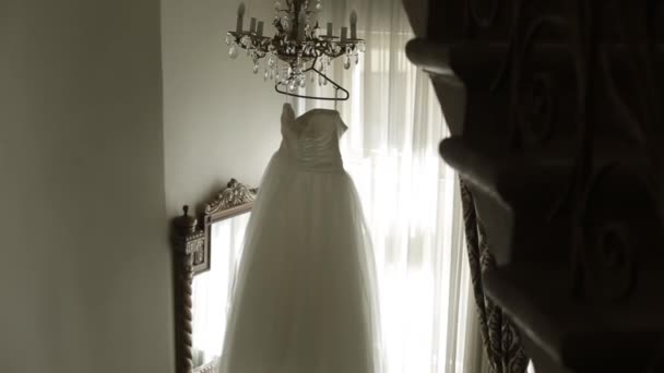 White wedding dress hanging in the corridor of the hotel next to the stairs