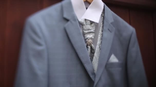 A mans gray jacket suit hanging in the yard hangs on a hanger before the grooms wedding