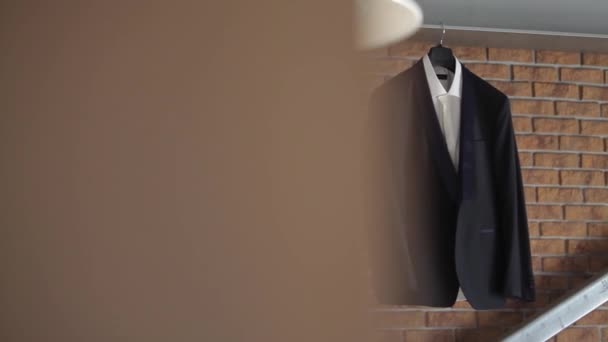 A mans jacket and suit hangs on a hanger before the grooms wedding