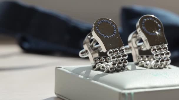 Stříbrné Manžetové knoflíčky mužské pro shirton na stole na bílé stojí detailní makro jezdce