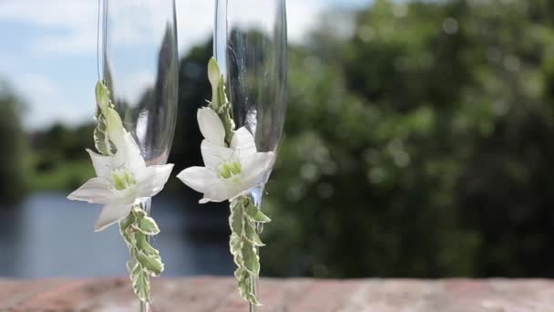 Wedding glasses with flowers near the water summer day