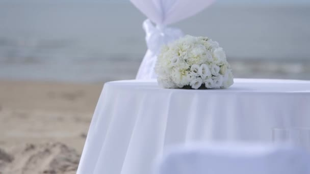 Decorazioni di nozze di tessuti bianchi e fiori sulla spiaggia prima della cerimonia
