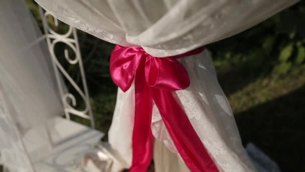 Wedding decorations of white fabrics and red tape before the ceremony