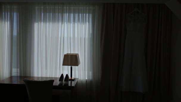 Svatební šaty v hotelu visí na zdi s přirozeným světlem
