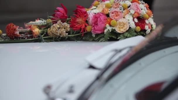 Bílé svatební auto bílé květy a fialové stuhy pověsit autem
