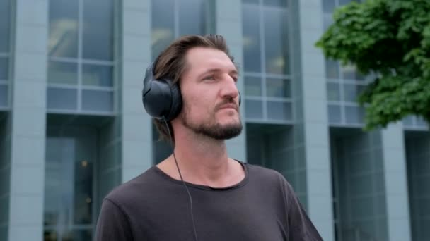 Poslech hudby nezávislý člověk ve velkém městském městě pracujícím s fotoaparátem a sluchátky pro přenosné počítače
