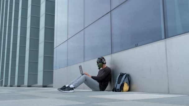 A man in a gas mask in the city with a laptop phone and headphones