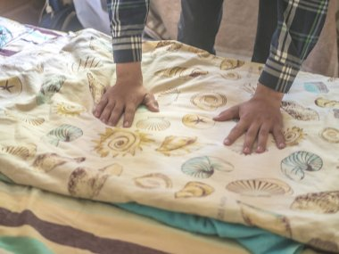 close up hands on a new bed textile blanket
