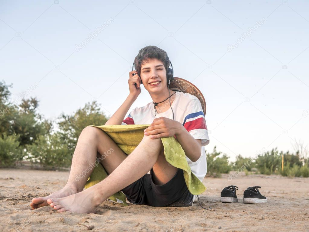 young hipster chilling on the beach sand on summer day listen music with headphones