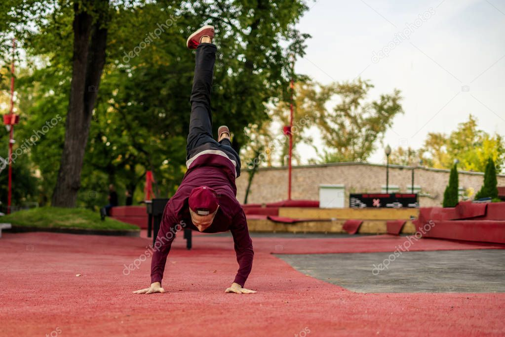 male athlete practising parkour in the street in summer day b