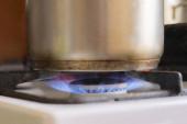 práce obrn eith hořící plyn a pánev s vroucí chutnou potravou, domácí kuchyně
