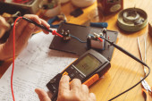 Photo process of making electrical measurements with multimeter, testing the equipments