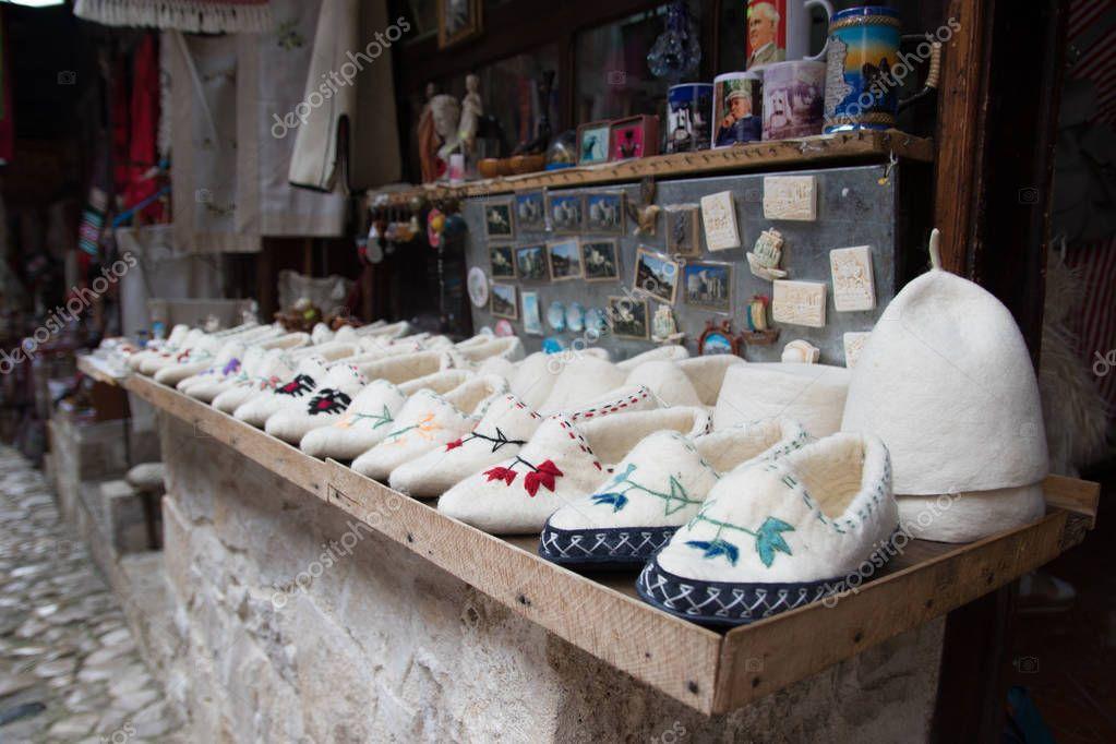 Kruje, Albania - June 2018: Traditional Ottoman market in Kruja, birth town of National Hero Skanderbeg. Flea market in Albania. Wool craft souvenirs for sale.