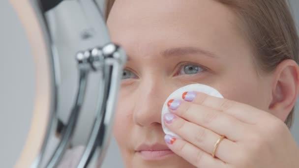 Kavkazský žena se zrcadlem s kroužkem světlem s žádný make-up vypadá zkoumat její kůži a dělá ošetření obličeje