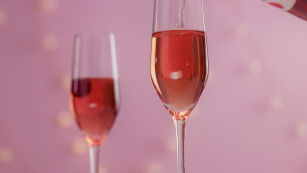 Pink sparkling wine with womans hand and glasses on pink background with christmas lights