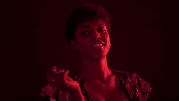 Frau im glitzernden Kleid in rotes Licht in Nachtclub
