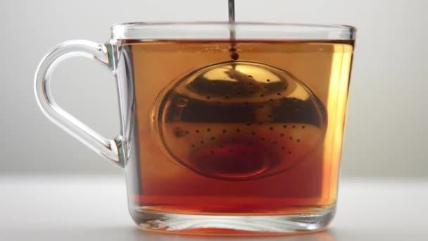 Průhledný šálek čaje v bílém studiu. Minimalistický čaj pro video vaření