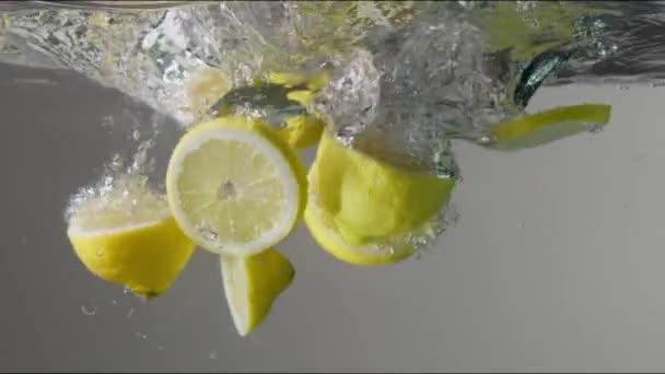 krájené citrony kapala do průhledného akvária s vodou na šedém pozadí