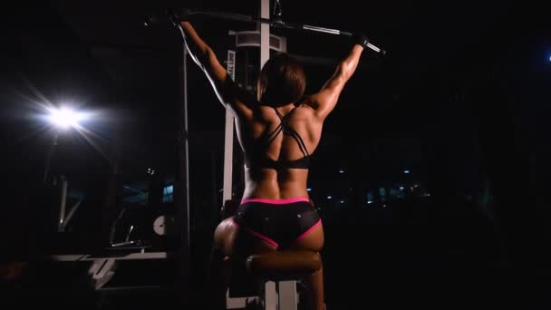 A strong, muscular, athletic bodybuilder girl, in short shorts, trains the back muscles on a horizontal simulator in a dark gym.