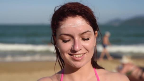 Portré egy gyönyörű fiatal nő, mosolyogva, a bikini, maszatos arc Napvédő krém, a tenger hátterét. Nő alkalmazása Sun Cream az arcon. Leégés.
