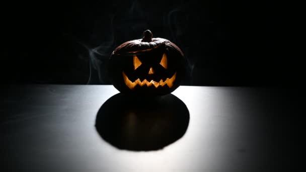 Halloween, pomerančová dýně s strašidelně světélkující tváří na tmavém pozadí. Šedý hustý kouř vychází.