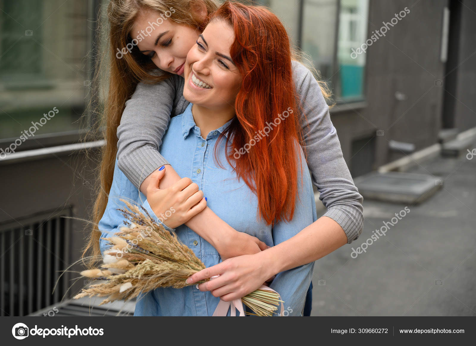Close Up Of Lesbian Couple Embracing In The Bedplay Phone Happily Stock Photo