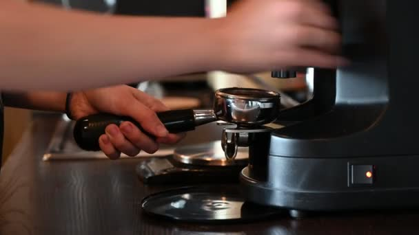 A woman pours ground coffee beans to make a cappuccino in a coffee machine. Close plan of barista hands preparing tonic drink in cafe. The cuisine in the restaurant.