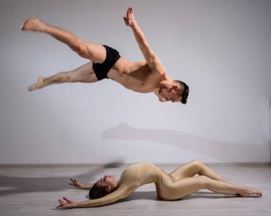 Acrobatic couple perform number on a white background. A duet of gymnasts rehearsing a performance with support. A man and a very flexible woman are dancing.