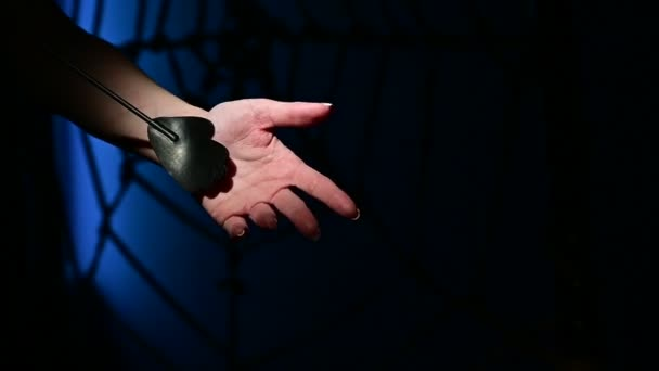 Nerozpoznatelná žena předvádí elegantní tenký kožený proužek v tmavé ložnici. Detailní záběr ženských rukou s hračkou bdsm. Bolest a požitek.Dospělá hračka na facky.