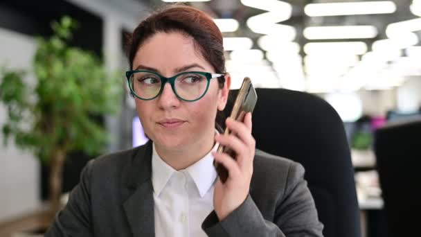 A woman sits in an office at her desk and gossips on the phone. Corporate ethics. Female employee in a suit tells secrets on a smartphone at work.