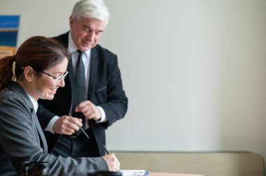 A woman in a suit signs documents under the direction of a mature male boss. Friendly colleagues talking in the office. A businessman teaches a subordinate.