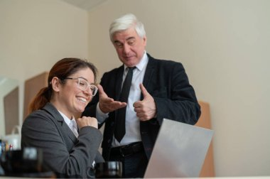 A mature male boss praises a subordinate. A woman in a suit works at a laptop at a desk. Friendly colleagues chat in the office.