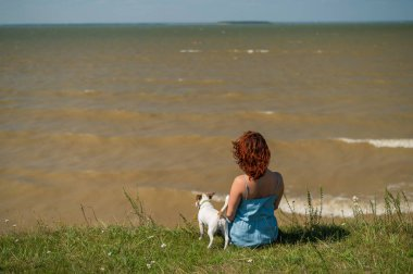 A woman sits on the bank of the river with a dog. Back view of a girl having a rest in nature with a pet.