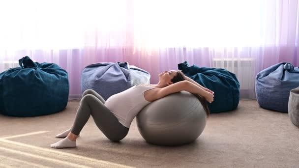 Eine schwangere Frau liegt auf einem Fitnessball. Eine Frau im dritten Trimester treibt Sport. Pilates für werdende Mütter.