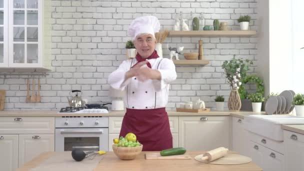 Starší muž kuchař pózuje v kuchyni