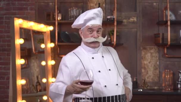 Muž kuchař cinknutí sklenice vína s fotoaparátem