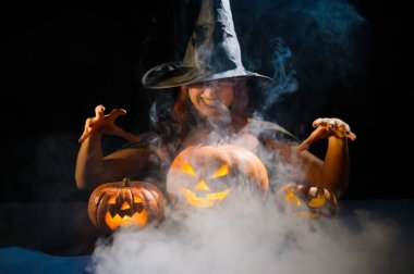 The evil witch casts a spell on pumpkins. Portrait of a woman in a carnival halloween costume in the dark