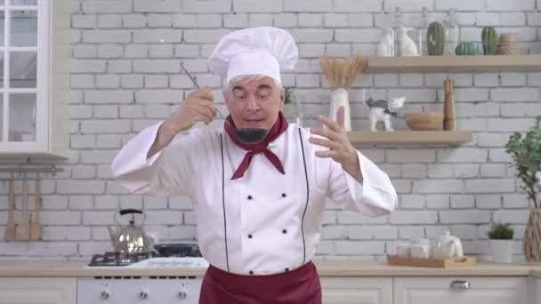 Kuchař si vychutnává vůni polévky a ochutnává ji z naběračky v kuchyni