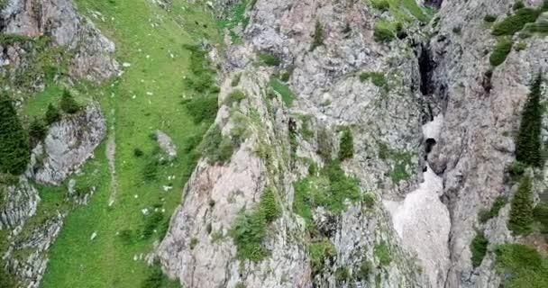 Blick von oben auf steile Bergklippen und eine Eishöhle.