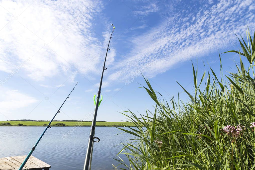 Hobbies, seasonal leisure and outdoor activities in the summer outdoors. Fishing on the shore of the reservoir, a fishermans rig next to the reeds on the lake, two rods against the blue sky.