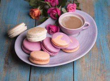 Colorful macaroons, cup of coffee and roses flowers on wooden background stock vector