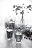 Fotografie monochrome photo of glass teapot and cups with floral and herbal tea