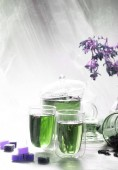 Fotografie Glass teapot and cups with green floral and herbal tea