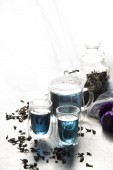 Glass teapot and cups with blue floral and herbal tea