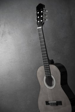 monochrome photo of acoustic guitar on grey background