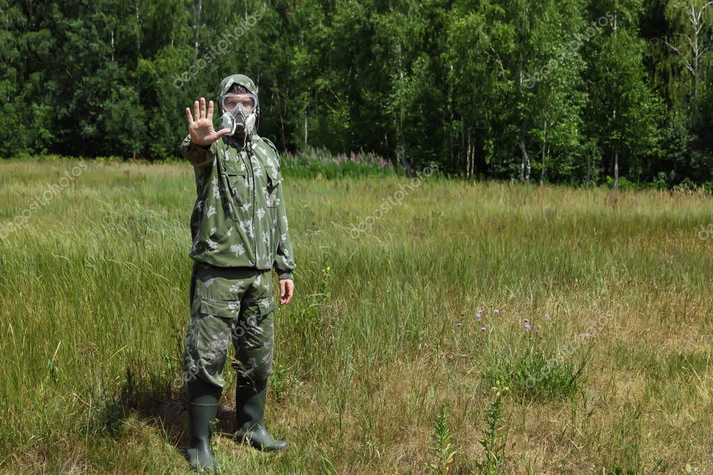 A man in a respirator and glasses and a camouflage suit against the background of nature. Chemical armies.