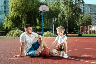 Father and son play basketball together at the basketball court. father spends time with the child, sporty lifestyle, training, rest, vacation.
