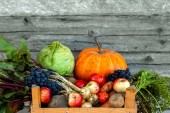 Wooden box with fresh vegetables and fruits, close-up, organic vegetables. The concept of a garden, cottage, harvest.